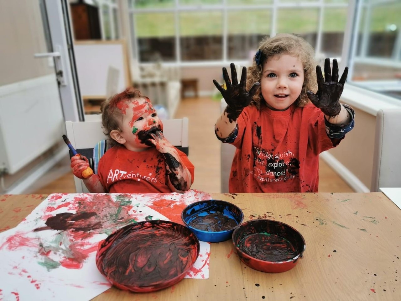 toddler and baby with paint on their hands and faces