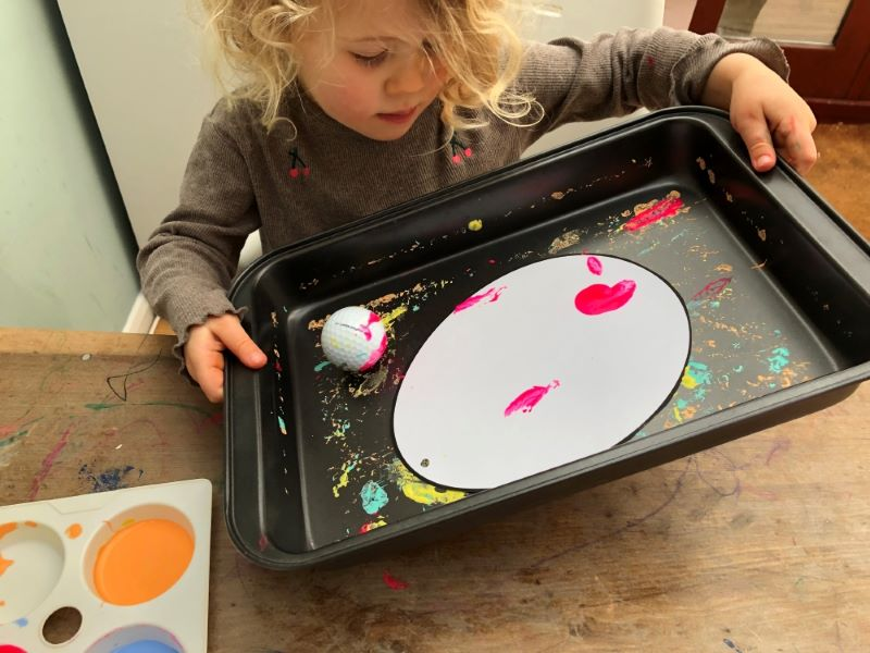 rolling a ball in a tray with paint on it