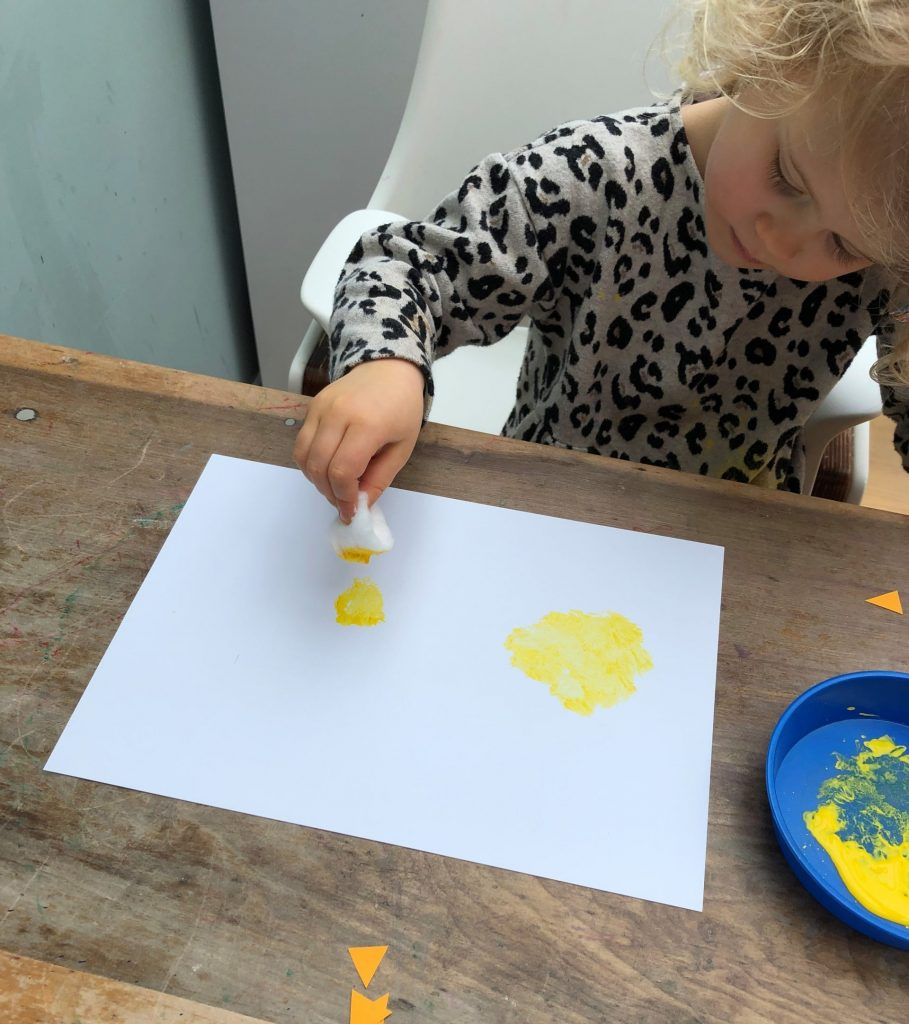 child dipping cotton wool in paint and dabbing it on paper
