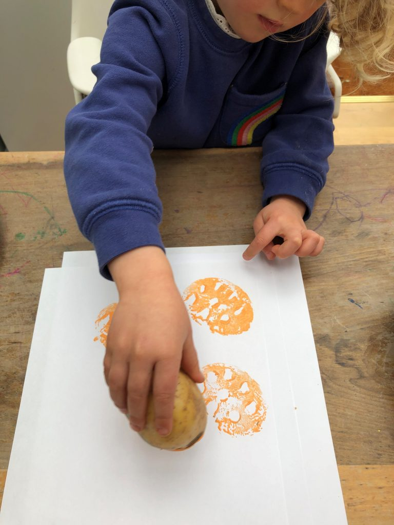 child stamping potato onto paper with paint on it