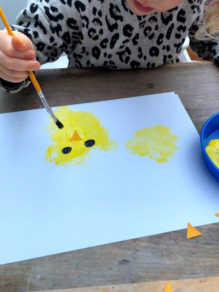 child painting eyes onto a painted chick on paper