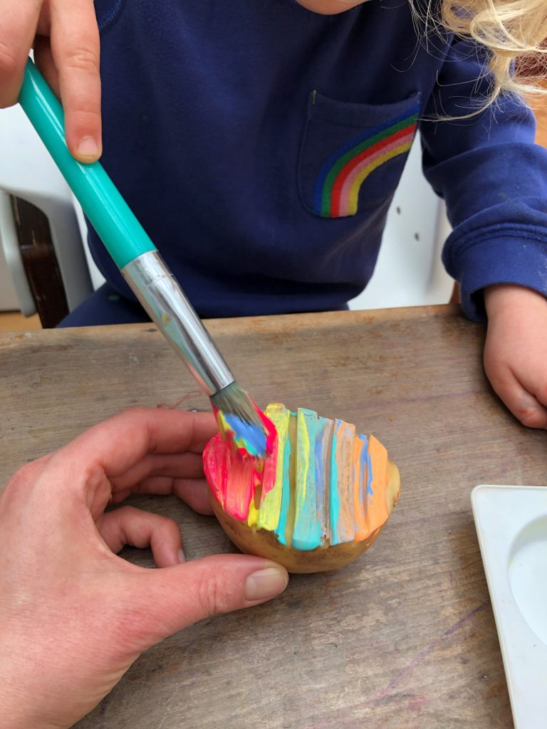 painting potato different colours with a paintbrush